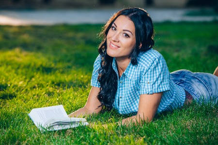 autodidact: beautiful girl with book in the autumn park.