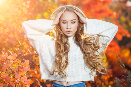 beautiful young woman with curly hair against a background of red and yellow autumn leaves.