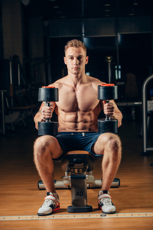muscle guy: Athlete muscular bodybuilder training back with dumbbell  in the gym.