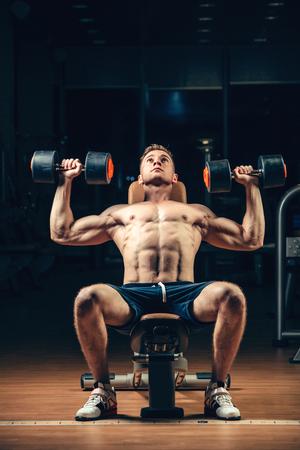 bodybuilder: Atleta entrenamiento culturista parte posterior muscular con pesas en el gimnasio.