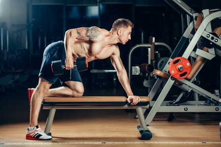 powerful man: Athlete muscular bodybuilder training back with dumbbell  in the gym.