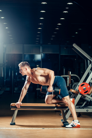 man power: Athlete muscular bodybuilder training back with dumbbell  in the gym.