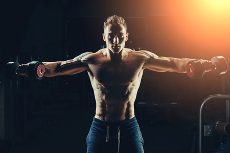 musculoso: Atleta entrenamiento culturista parte posterior muscular con pesas en el gimnasio.