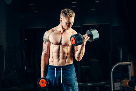 Athlete muscular bodybuilder training back with dumbbell  in the gym.
