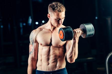 figura humana: Atleta entrenamiento culturista parte posterior muscular con pesas en el gimnasio.