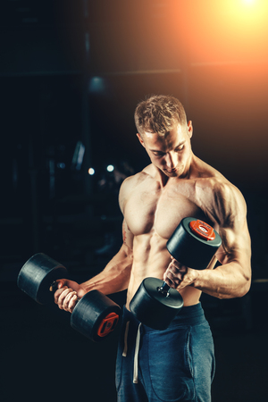 muscular body: Athlete muscular bodybuilder training back with dumbbell  in the gym.