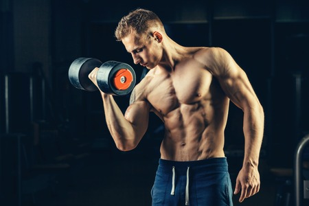 pectoral muscle: Athlete muscular bodybuilder training back with dumbbell  in the gym.