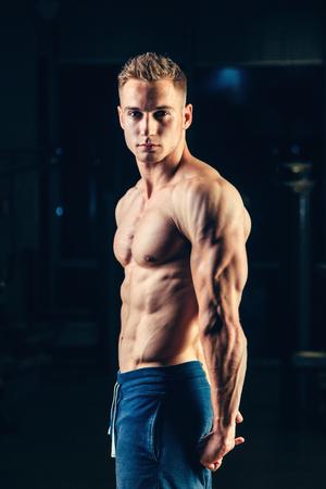 poses de modelos: Silueta de un atleta fuerte. Hombre confidente joven de la aptitud con las manos fuertes. Luz dram�tico