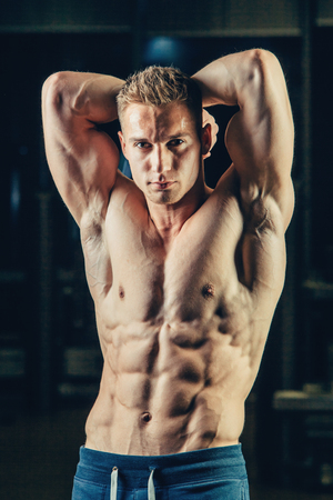 muscular body: Silhouette of a strong athlete. Confident young fitness man with strong hands. Dramatic light