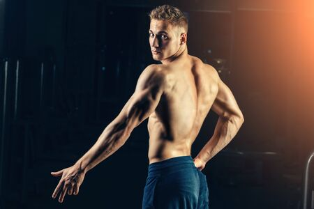nipple man: Silhouette of a athlete. Confident young fitness man with strong hands. Dramatic light Stock Photo
