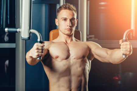 crossover: Brutal athletic man pumping up muscles on crossover.