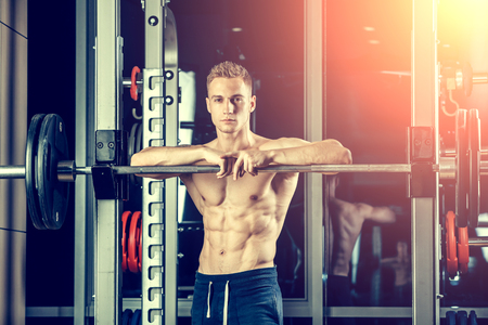 abs: Closeup portrait of a muscular man workout with barbell at gym. Brutal bodybuilder athletic man with six pack, perfect abs, shoulders, biceps, triceps and chest