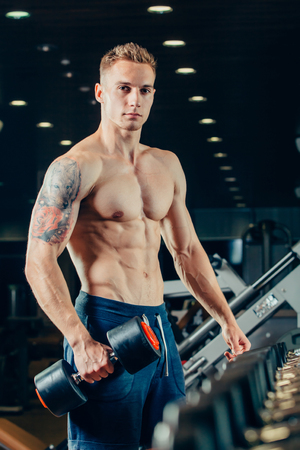 male body: Male athlete with a dumbbell in the gym lean on dumbbell row
