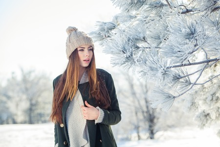 cold background: Beautiful winter portrait of young woman in the winter snowy scenery.