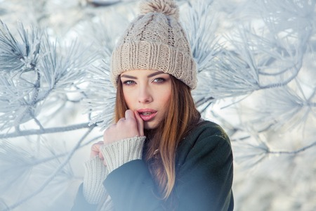 Beautiful winter portrait of young woman in the winter snowy scenery.