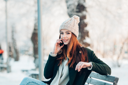 mobile sms: Young  woman smiling with smart phone and winter landscape