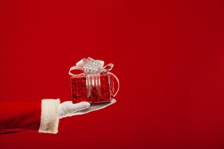 dar un regalo: Foto de Santa Claus mano enguantada con caja de regalo de color rojo, sobre un fondo rojo