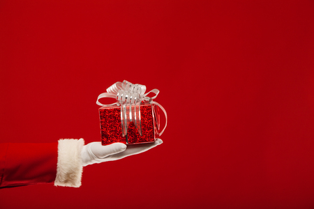 giving gift: Photo of Santa Claus gloved hand with red giftbox, on a red background Stock Photo