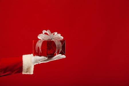 Foto van de Kerstman gehandschoende hand met rode giftbox, op een rode achtergrond Stockfoto