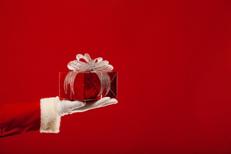 traditional gifts: Photo of Santa Claus gloved hand with red giftbox, on a red background Stock Photo