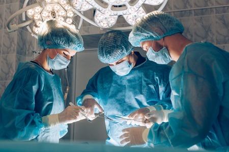 quir�rgico: Cirujanos equipo que trabaja con la supervisi�n del paciente en la sala de operaciones quir�rgicas