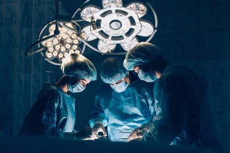 cirujano: Cirujanos equipo que trabaja con la supervisi�n del paciente en la sala de operaciones quir�rgicas