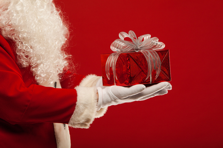 Photo of Santa Claus gloved hand with red giftbox on a red background Фото со стока