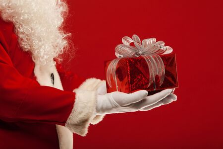 santaclaus: Photo of Santa Claus gloved hand with red giftbox on a red background Stock Photo