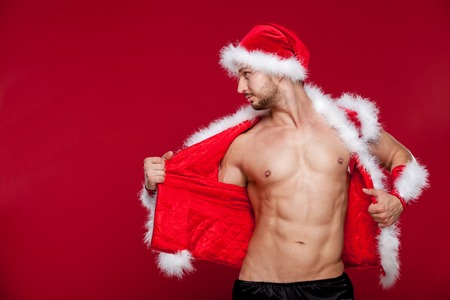man with hat: muscular man in santa uniform Stock Photo