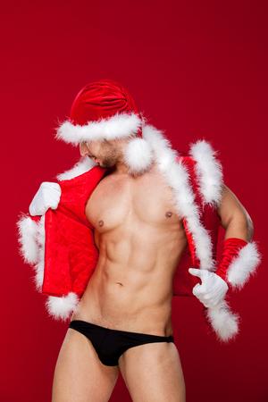 nude christmas: muscular man in santa uniform Stock Photo