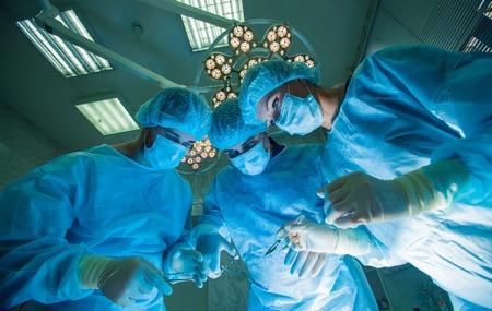 cirujano: Los cirujanos de pie encima del paciente antes de la cirug�a. Foto de archivo