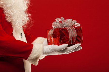 gloved: Photo of Santa Claus gloved hand with red giftbox, on a red background Stock Photo