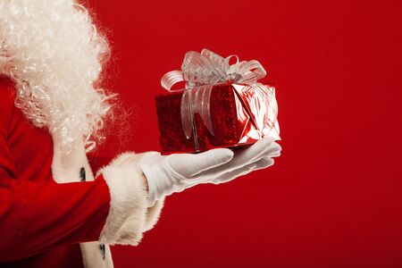 Photo of Santa Claus gloved hand with red giftbox, on a red background Фото со стока