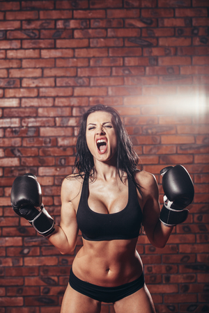 girl punch: Young sexy girl with boxing gloves, on the background wall of red brick