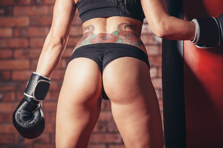 female fighter: Young sexy girl with boxing gloves. punching bag on the background wall of red brick. Stock Photo
