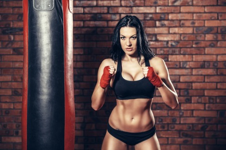 Young beautiful sexy boxer woman with red boxing bandage on hands. Standard-Bild