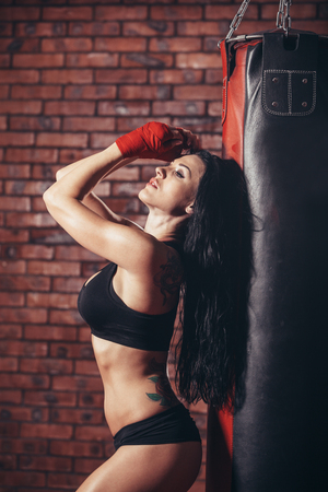 punching bag: Young beautiful sexy boxer woman with red boxing bandage on hands. punching bag on the background wall of red brick.