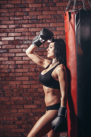 punching bag: Young sexy girl with boxing gloves. punching bag on the background wall of red brick. Stock Photo