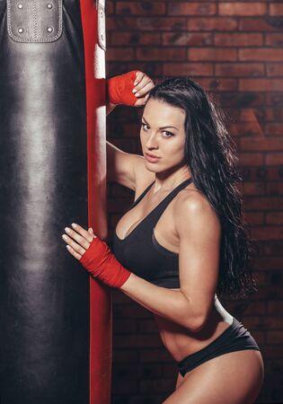 chica sexy: Mujer hermosa joven boxeador sexy con el vendaje de boxeo rojo en las manos. saco de boxeo en el fondo de la pared de ladrillo rojo.