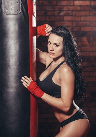 Young beautiful sexy boxer woman with red boxing bandage on hands. punching bag on the background wall of red brick.