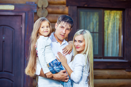 Happy young family near the wooden house. Stock Photo