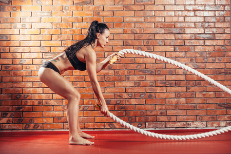 gym room: An attractive young and athletic girl using training ropes in a gym on the background wall of red brick.
