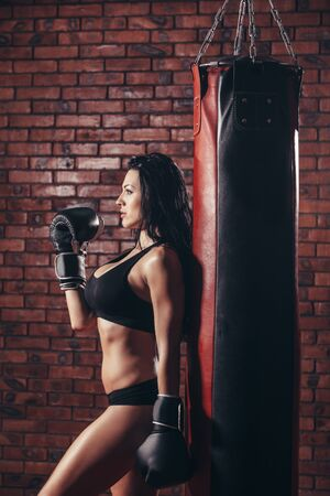 punching bag: Young sexy girl with boxing gloves, punching bag, on the background wall of red brick.