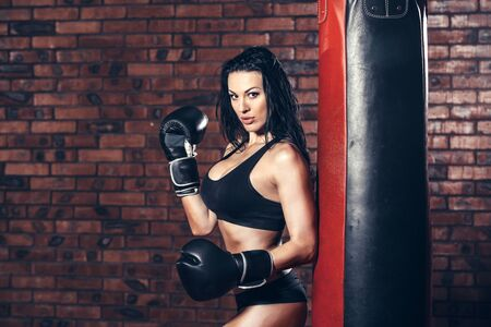 female boxing: Young sexy girl with boxing gloves, punching bag, on the background wall of red brick