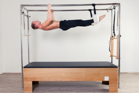aerobic instructor: Pilates aerobic instructor man in cadillac fitness exercise. Stock Photo