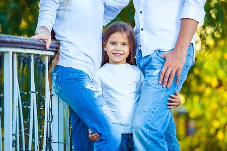 ni�as peque�as: very cute little blonde girl holding the foot mom and dad Foto de archivo