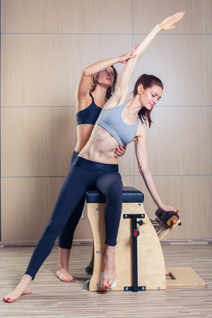 pilates woman: woman with instructor of fitness yoga exercise