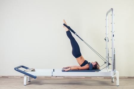 leisure equipment: Pilates reformer workout exercises woman brunette at gym indoor. Stock Photo