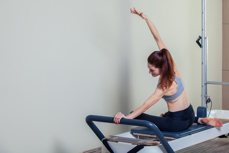 pilates woman: Pilates reformer workout exercises woman brunette at gym indoor. Stock Photo