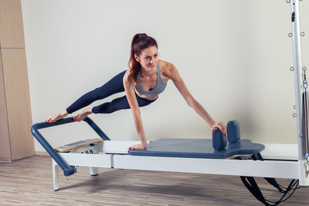 pilates: Pilates reformer workout exercises woman brunette at gym indoor. Stock Photo